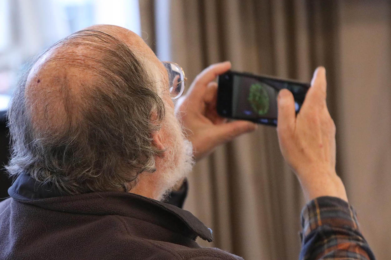 man taking photo of the slides during the event