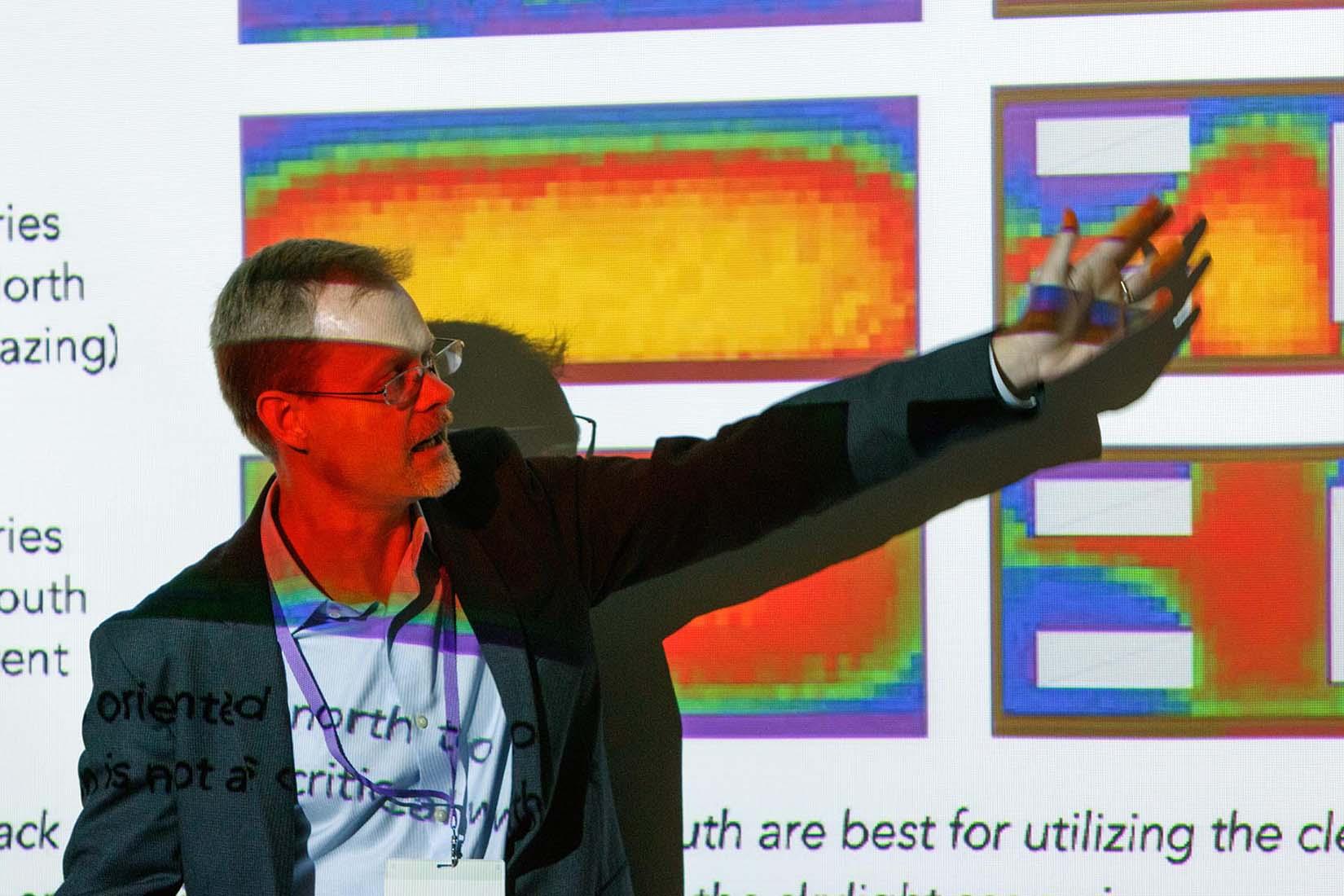 speaker pointing at the slideshow