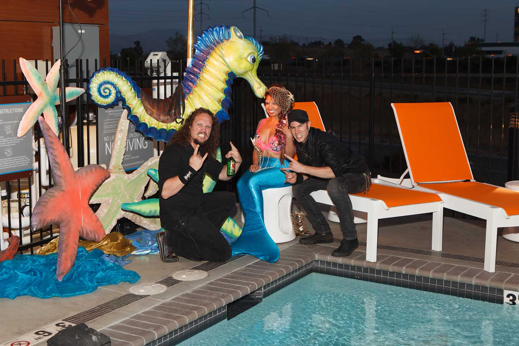 guests posing with a mermaid by the hotel pool