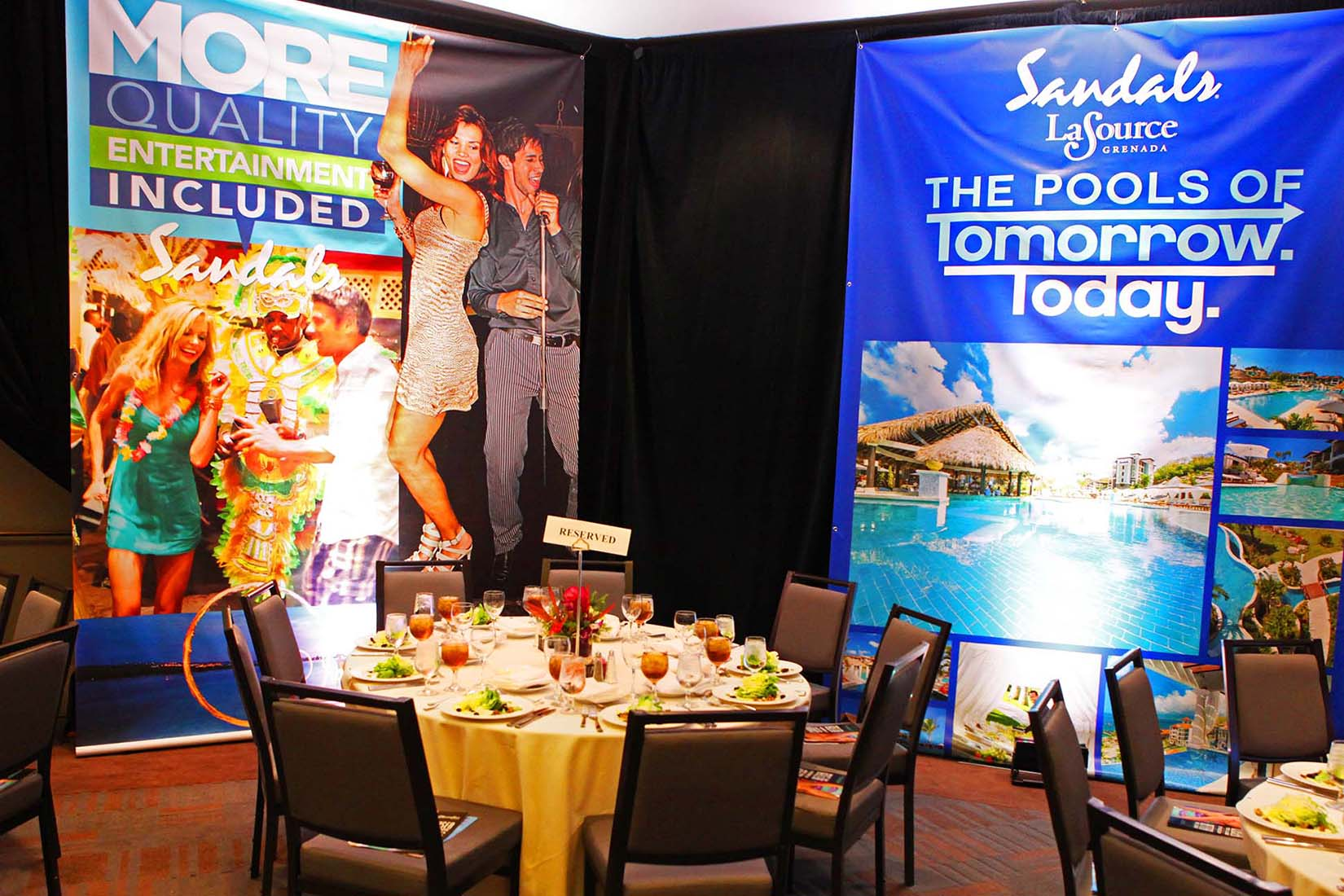 a table set up and sandals banners in the background